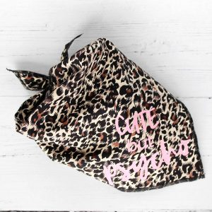 leopard print dog bandana with text in baby pink which says cute but psycho