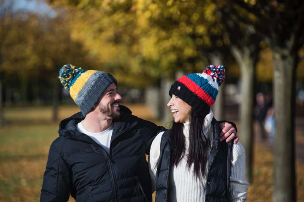 man and woman wearing bobble hats