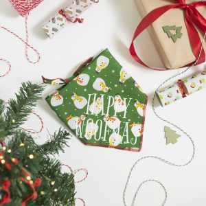 A Christmas Snowman green dog bandana with Happy Woofmas slogan in a Christmas flatlay