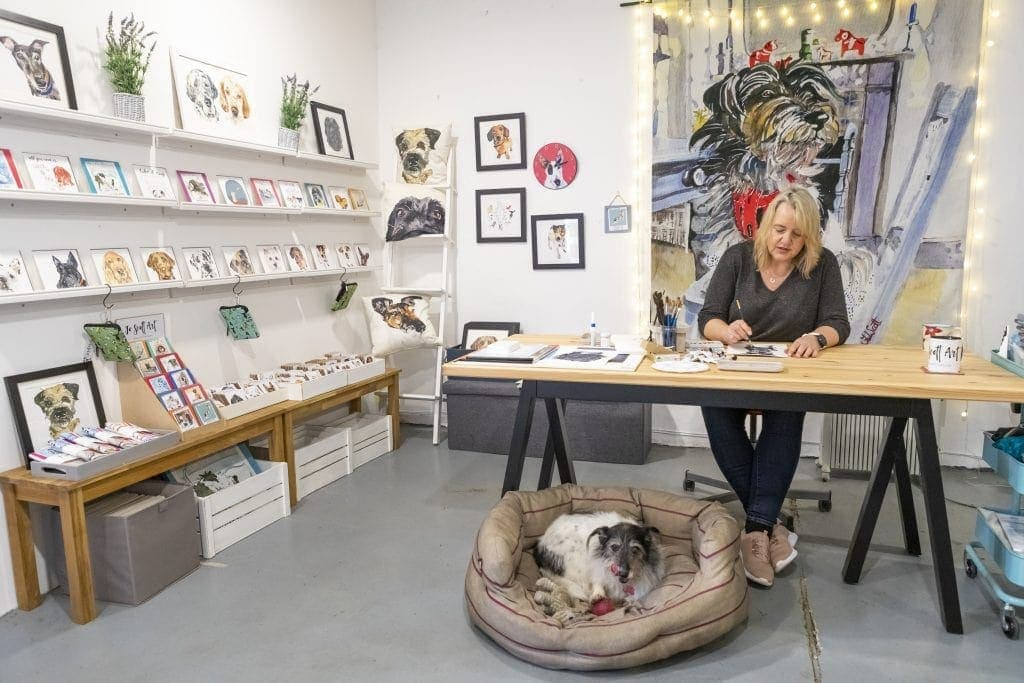 Jo Scott in her studio working on a painting with her dog at her feet