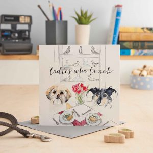 white square greeting card with a picture of two dogs at a table with food on it and text that says 'ladies who lunch'