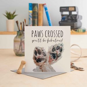white square greeting card with a picture of two dog paws crossed and text that says 'paws crossed you'll be fabulous!'