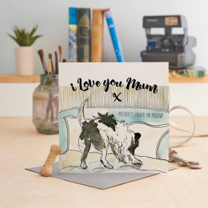 white square greeting card with 8 dog pictures and text saying I Love You Mum x (present's under the pillow!) with a black & white dog on a bed looking under the pillow