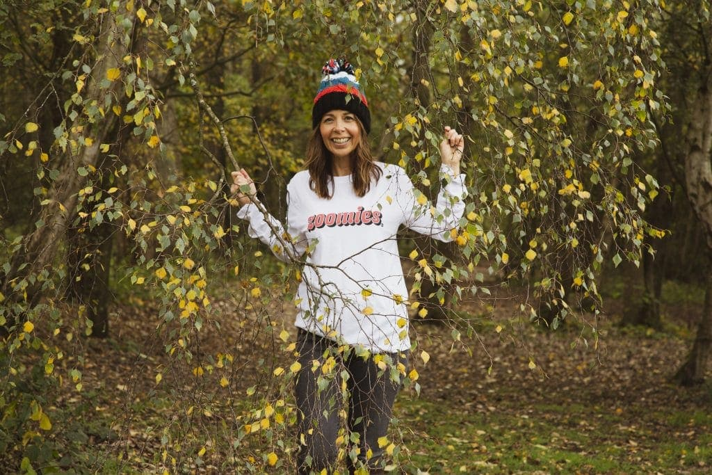 Woman standing amongst trees with a bobble hat and white top with zoomies on the front