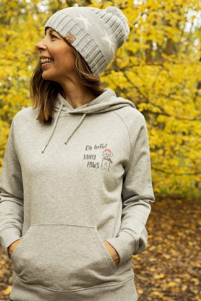 Woman wearing a grey hoodie with hello Santa Paws and a dog motif on the front