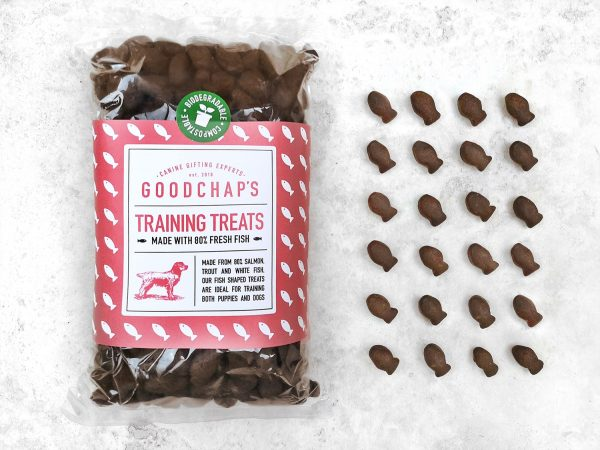 Packet of goodchap training treats on a white background with rows of the fish shamed treats laid out next to the packets